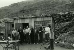 Ti menn foran en brakke i Hammerfest