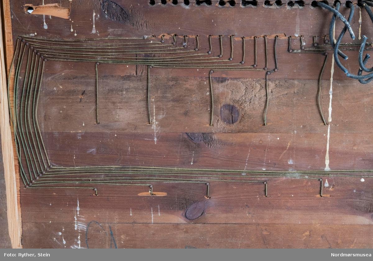 Signaltavle brukt til å sende beskjeder mellom etasjene i Festiviteten i Kristiansund. Pappskiver med tall er festet til en hendel som igjen er festet til en spole. Når spolen får strøm, aktiveres den og pappskiven løftes opp. Glasset er malt med svarte streker, slik at tallene som ikke er aktive blir skjult.