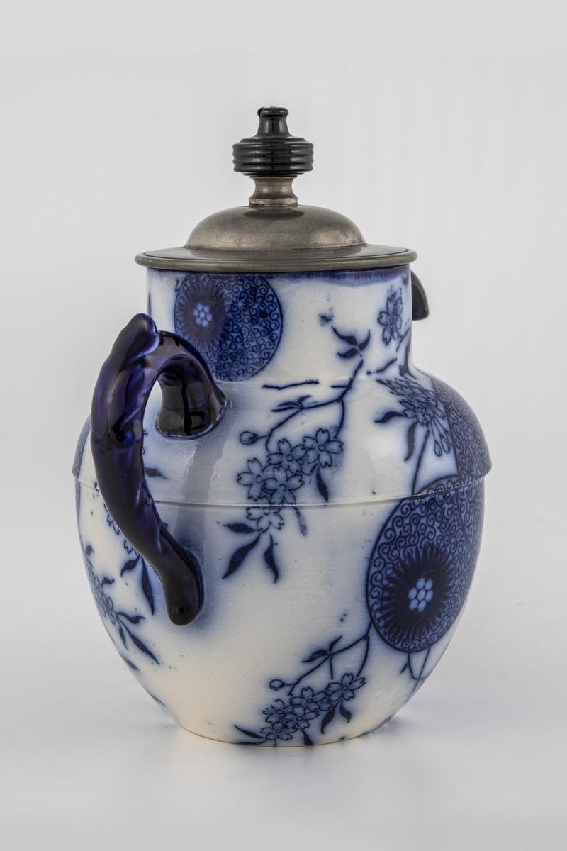 Kanne i glasert steintøy, dekorert med blåfarget trykkdekor. Tilnærmet kuleformet korpus og sylinderformet hals, dekorert med blåhvite blomstermotiver. Svungen tut og buet hank i mørkeblått. Sylinderformet lokk i tinn med sortfarget lokknapp.