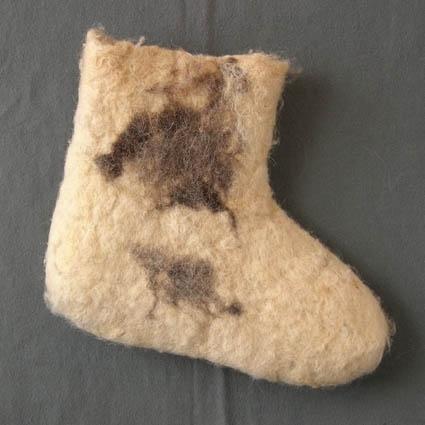 Socka tovad av naturvit ull, troligtvis ryaull, där locken fortfarande syns. Som dekoration är en fläck av naturgrå och natursvart ull intovad både på in- och utsidan av skaftet. Sockan är inte tovad så väldigt hårt och skaftets kant är naturligt avslutad och ojämn.