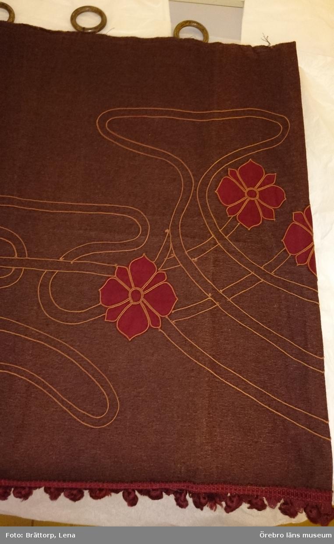 Dörröverstycke av rödbrunt ylletyg. Stycket är maskinbroderat i jugendmönster: slingor och applicerade mörkröda blommor. I nederkanten påsatt mönstrat ylleband med hängande tofsar.  Bredd 172-170 cm, Höjd 73 cm + tofsar. Fästa mormorsringar. Gåva av Maja Ajaxon.