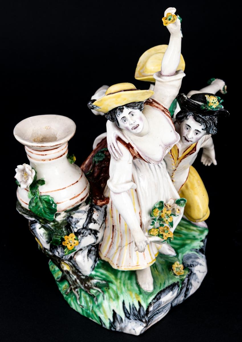 Figurgrupp. Herde och blomsterplockerskor, grupp av mjukt porslin. Märke: MB - Marieberg. Berthevins tid 1766-1769, oläsligt, H. F. (tillverkad av Hierner?)  Gruppen består av en mansfigur och två kvinnofigurer samt en urna på en trädstam. Målat i polykromoa färger - grönt, brunt och gult.