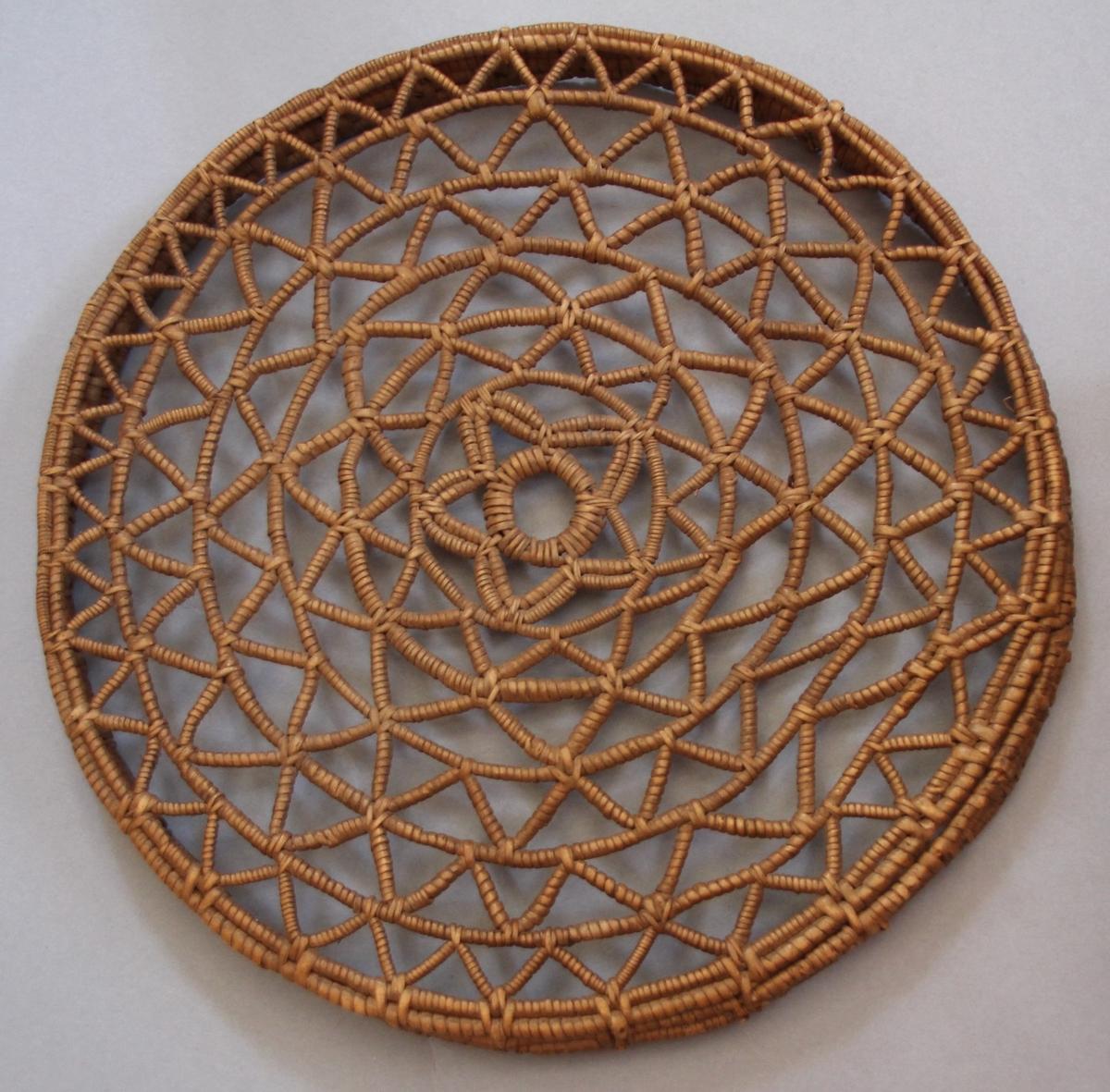 Rund korv i tægerarbeid med lok. Korga har ganske ope mønster, stjernemønster i midten av loket og botn. Trekantar, sirklar m.m. Nokre skadar øverst på korga.