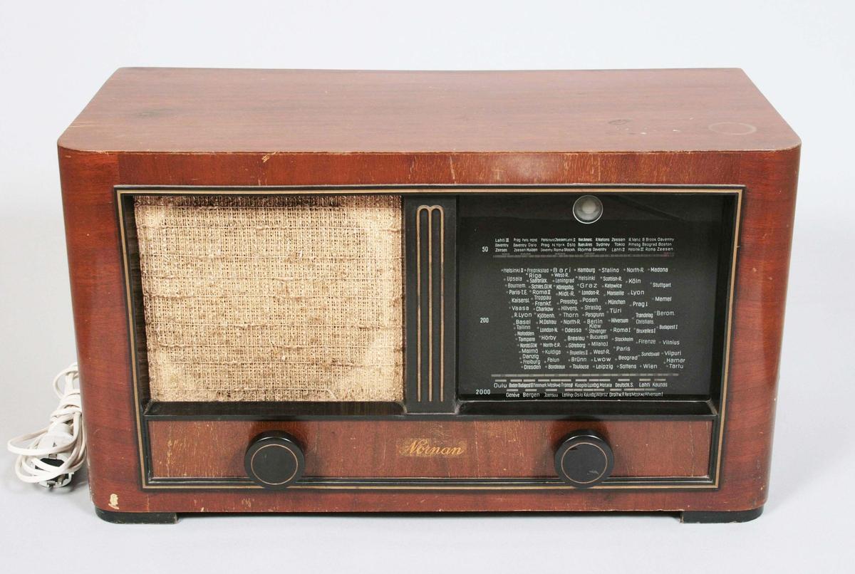 Radioapparat. Rektangulär med rundade framhörn. Brunfanerad. Framsidan med ram. På vänster sida högtalare och på höger sida frekvenstavla bakom glas, med namn på städer. På undersidan, två bakelitrattar, den vänstra för volymen och den högra för frekvensen (LV, MV, KV). Nätansluten. Märkt: Nornan. Proveniens Munin Kläder, Borås.  Historik:  Nornan radioapparater, monterades ihop och tillverkades vid Tobo bruk, men det egentliga företaget bakom, var Svenska cykelfabriken Monark i Varberg.