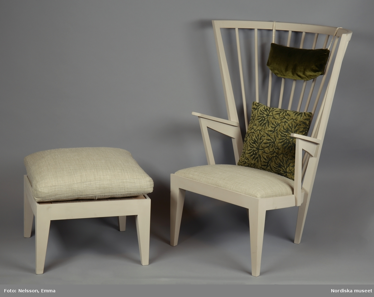 Länstol, av bok målad i ljusgrå äggoljetempera. Omslutande hög rygg med tio rundsvaravde spjälor, öppna armlän och fyra fyrkantiga, nedåt avsmalnande ben. Infälld sits med klädsel av beige linneväv (A:2), nackkudde (C), kudde (D) samt tillhörande fotpall (B:1-3). /Anna Arfvidsson Womack 2021-08-17