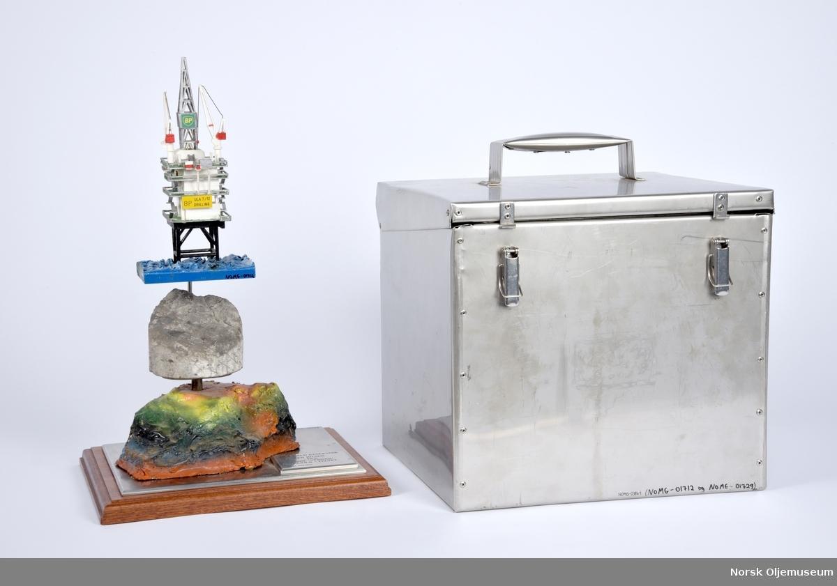Modell bestående av to deler. Den øverste delen er en modell av boreplattformen DP på Ulafeltet. Den nederste delen symboliserer Ula reservoaret med en kjerneprøve på toppen. De to delene kobles sammen.   Modellen har en tilpasset oppbevaringskasse med løs skuff.