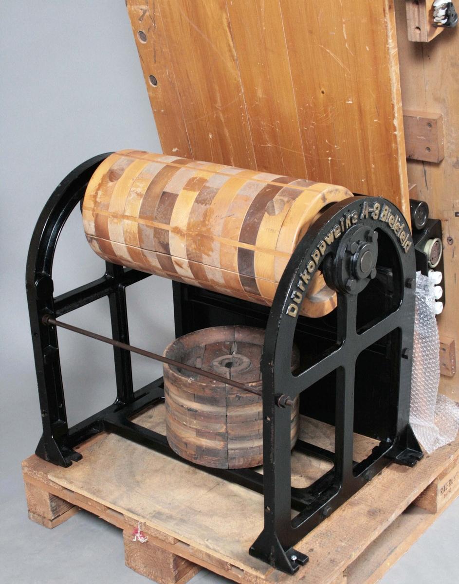 Löpande band. Gjutjärnsstativ med drivrullar av trä. Träbord. 2 änddelar, varav den ena är drivande. Mellan dessa finns bordsskivor av trä på vilka duken, som transporterar plaggen har vilat. Strömuttag för symaskinerna finns på stativen. Drivrullarna av limmat trä. 1-2 Änddelar, 10 bordsskivor, 11 stativdelar, propptavla. Skyddskåpa i metall för änddel. Märkt: DÜRKOPPWERKE A.G. BIELFELDT. Proveniens J.A. Peterson, Målsryd.