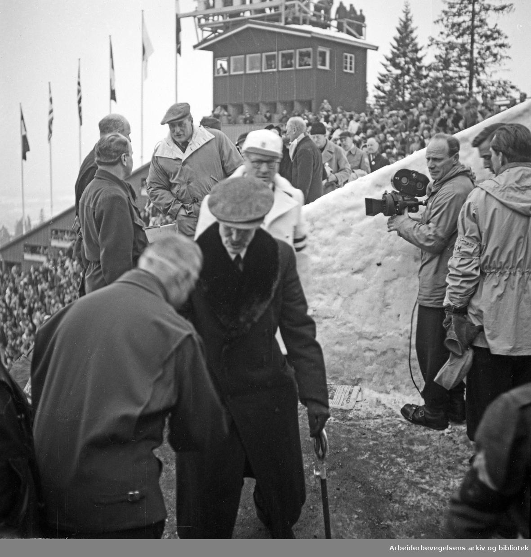 De sjette olympiske vinterleker, Oslo 14.-25. februar 1952. Kong Haakon VII, president i den internasjonale olympiske komité, Avery Brundage og Kronprins Olav på tribunen i Holmenkollen. Til høyre med filmkamera: Finn Bergan.