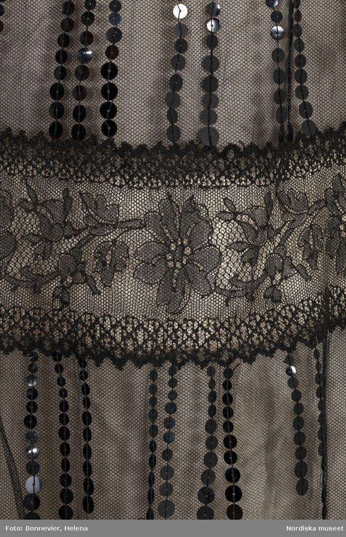 Klänning monterad på docka. NK:s Franska damskrädderi. Hellång korsetterad aftonklänning skuren i ett stycke av svart silkestyll, spets och paljetter över gräddvit satäng. Sammetsbård nedtill. Troligen beställd av Louise Wachtmeister af Johannishus född af Ugglas (1859-1943). Levererad 1902-1905. Röhsska konstmuseet. RKM 184-1997.