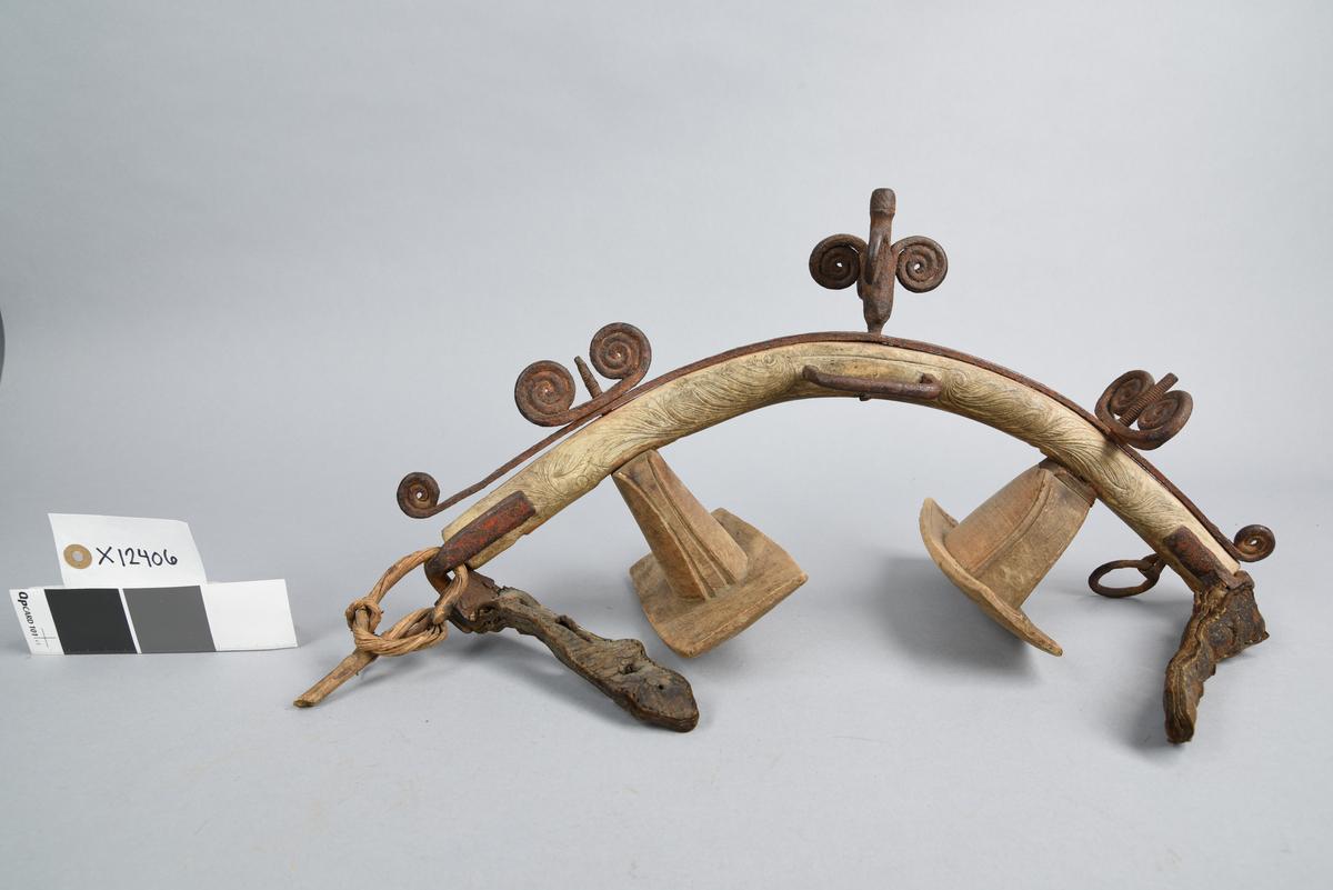 """X 12406 Fra protokoll: """"Høvre av ben med skåret bladranke. Overkanten beslått med jernbånd med rester av rød maling; som toppornament en 7 cm høi pigg av jern med fire spiralformede utløpere; spiralformede skrusnorer på oversiden til feste av bæreputene.#Falsk datert """"'1610""""."""""""