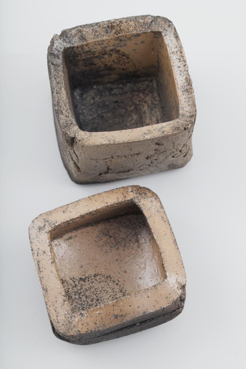 Rektangulær boks med lavt lokk i rakubrent leire. Relativt monokrom med brune nyanser fra lys brun til nesten svart. Matt uglasert utsiden, men glasert på innsiden. Beigeaktig i glasurfargen på innsiden. Boksen er grov og enkel i uttrykket med en del fine sprekker som er oppstått under brenningen.  Inngravert med fem streker på undersiden.