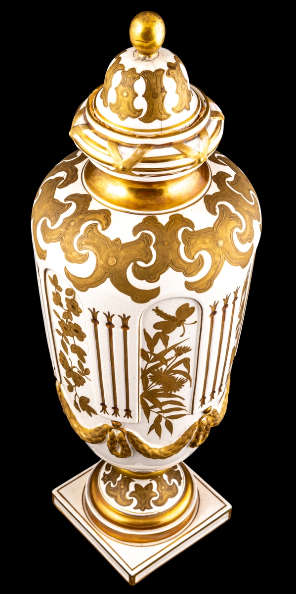 Urna av porslin med gustaviansk dekor i form av blommor och blad med girland. Dekoren är förgylld och bronserad. Försedd med lock med förgylld knopp. På undersidan av foten står Gustafsberg 1894.  Stämpel: ankare.