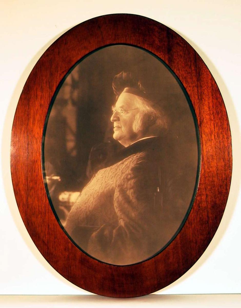 Portettfotografi i profil av eldre mann med barett, briller, og hjemmefrakk med sjalskrave.