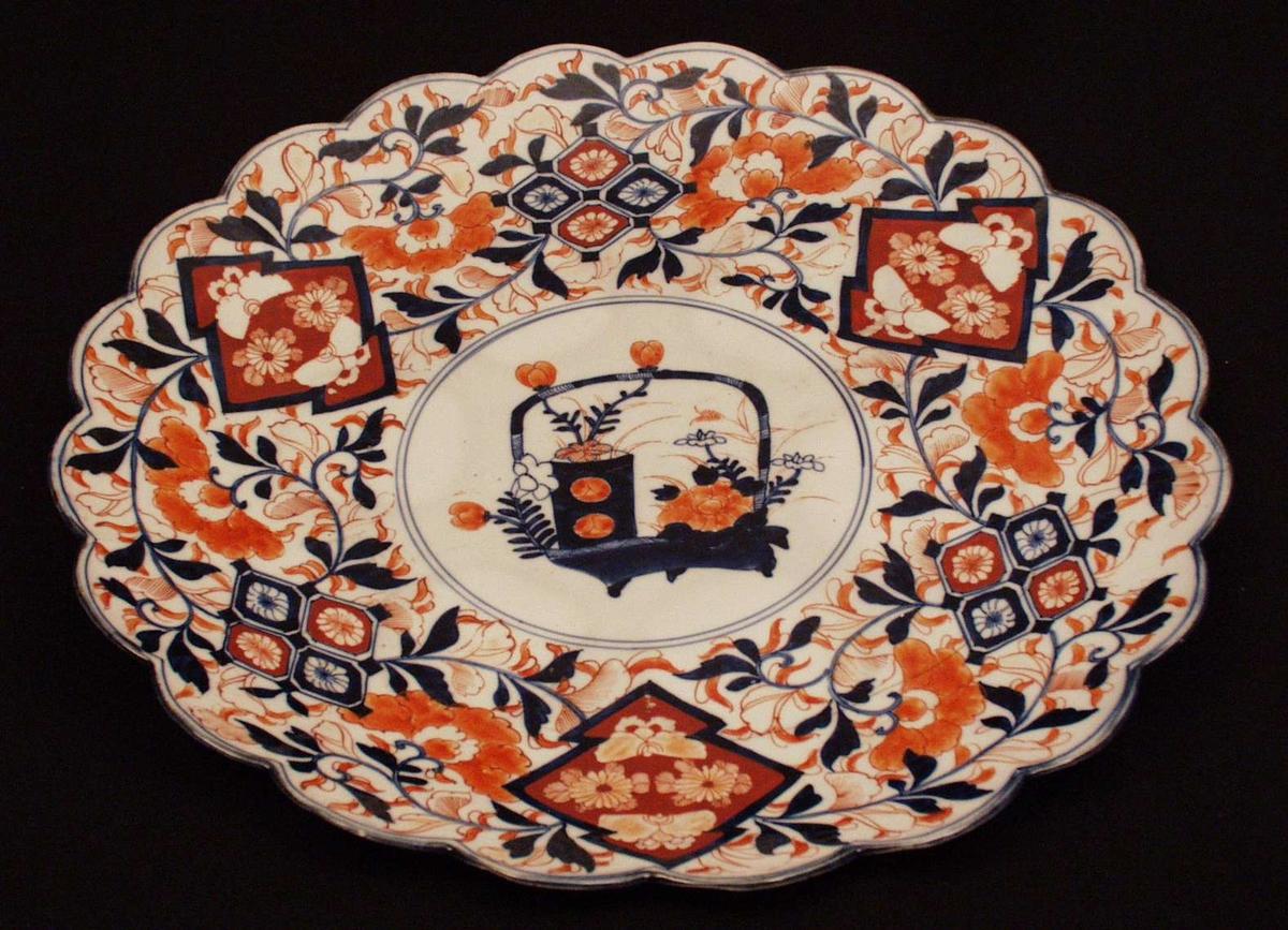 Dekormotiv: blå vase m. rødbrune blomsteter, rundt stilisert mønster i sjatert blå og rødbrune farger, bred og smal blå rans langs kant, midtparti: 2 blå render i sirkler, undersiden dekorert i blått m. linjer og blomster. Tungekantet.