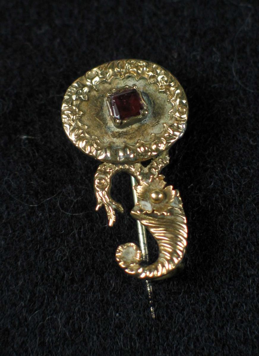 Gullnål med rød firkantet stein på oval plate med bladkrans. Rillet underdel med blomst.