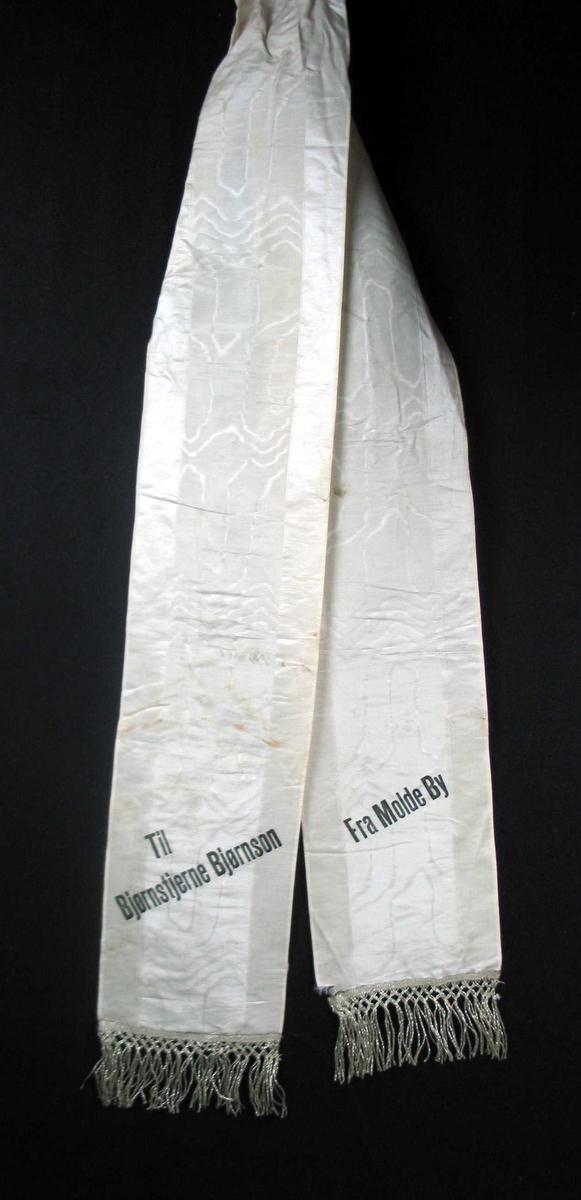 Begravelsessløyfe i mønstret hvit silke med frynser.