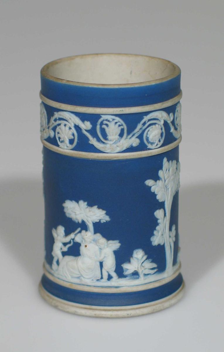 Vase i biskuit, hvite relieffer på blå bunn. Sylinderformet med hvitt fotstykke.