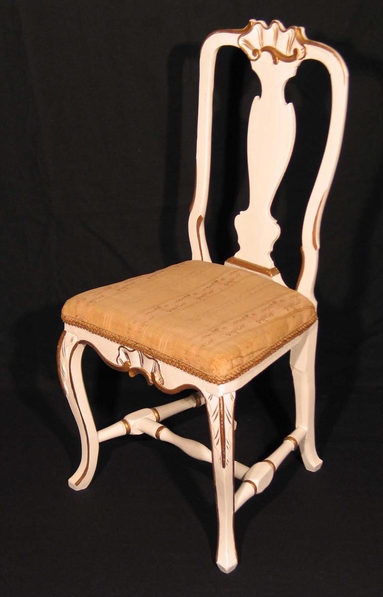 Hvitmalt stol i bjørk med utskåret muslingmønster på toppstykke og sarg. Også utskåret ryggbrett og sprosser. Svungne forben.Bronsemalte detaljer. Setet er trukket om i brokadestoff (skaffet av Dagny.)