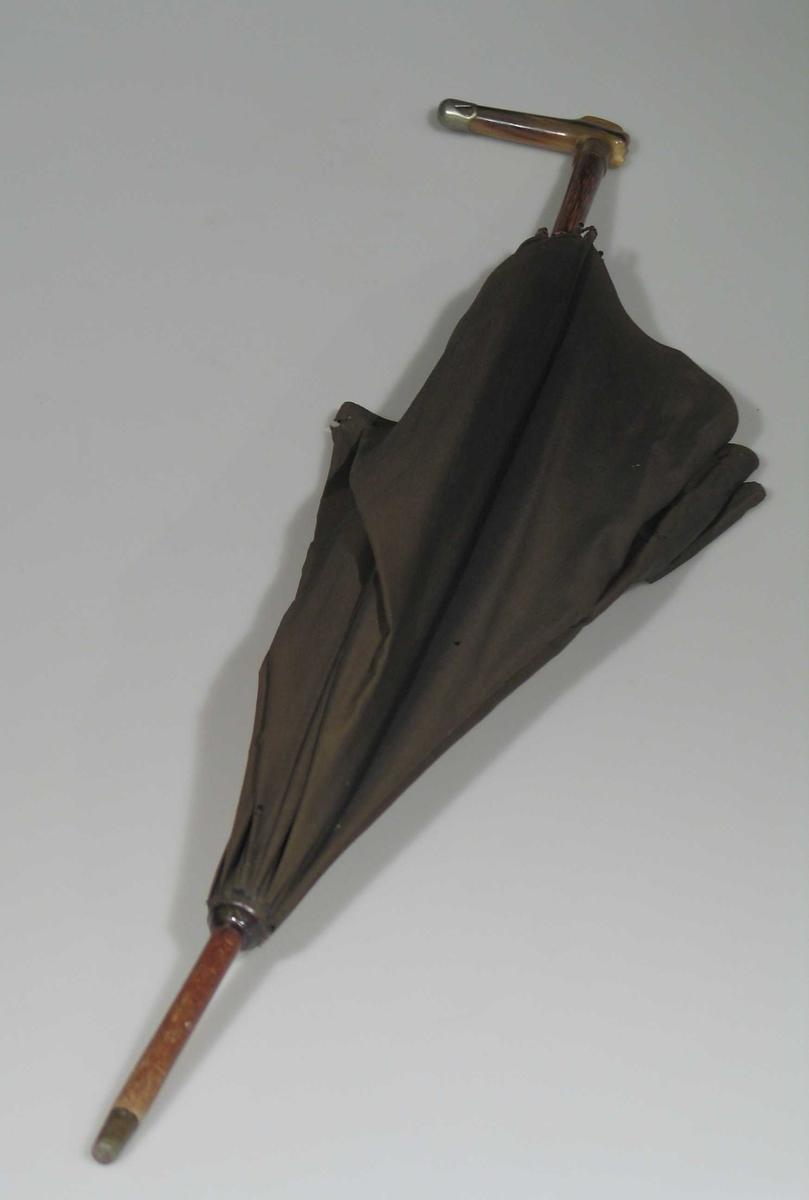 Svart paraply i silke der beinskaftet har metallbeslag.