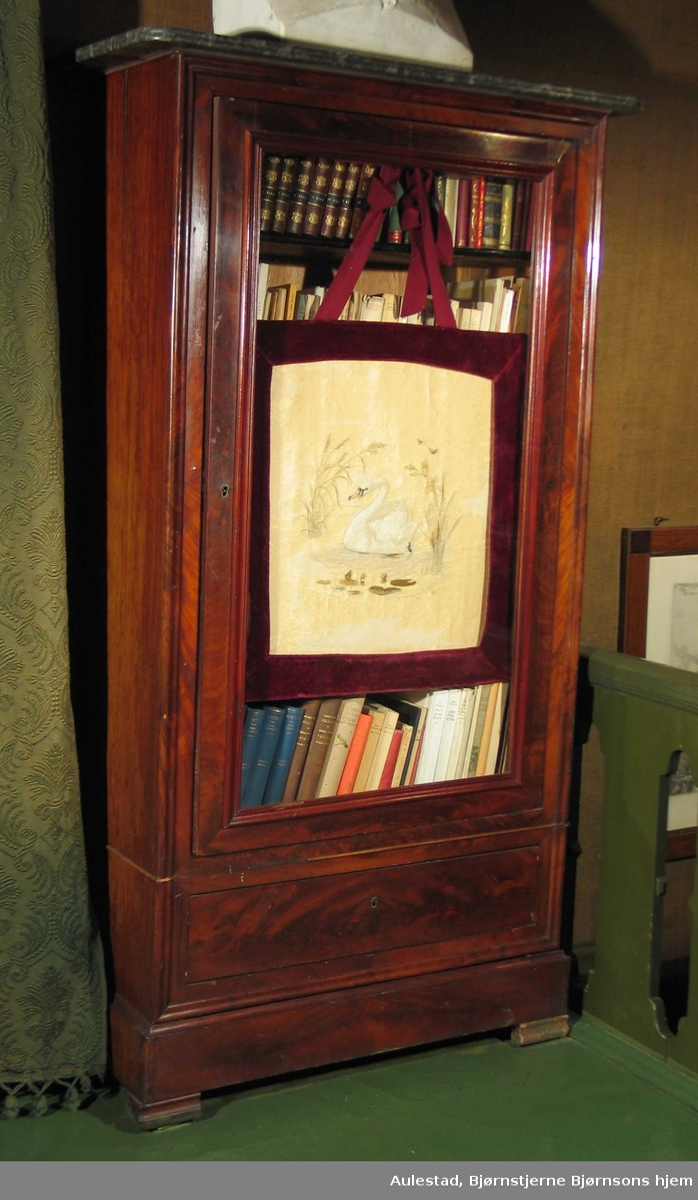 Bokskap i brunbeiset finert tre, antatt mahogny med plate i svart marmor, glassdør og skuff nederst. Skapet har hyller og står på lave, firkantete bein. Platen har en slipt stripe og avrundede hjørner. Døren har rike listprofiler.