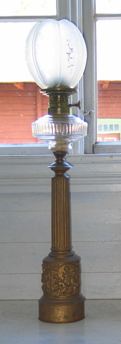 Parafinlampe i metall med klassisk søyleformet understell. Brenselbeholderen er i klart glass med slipt dekor. Kuppelen er tulipanformet og har mattslipt rankedekor. På sokkelen er det tre scener med amoriner. Gjennombrutt mønster på brenneren.
