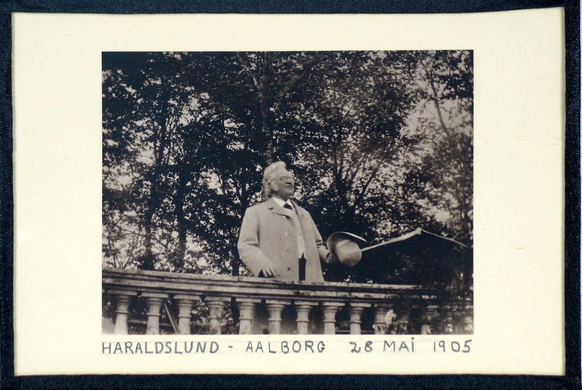 Fotografi med håndskrevet bildetekst, glass og svart shirting.
