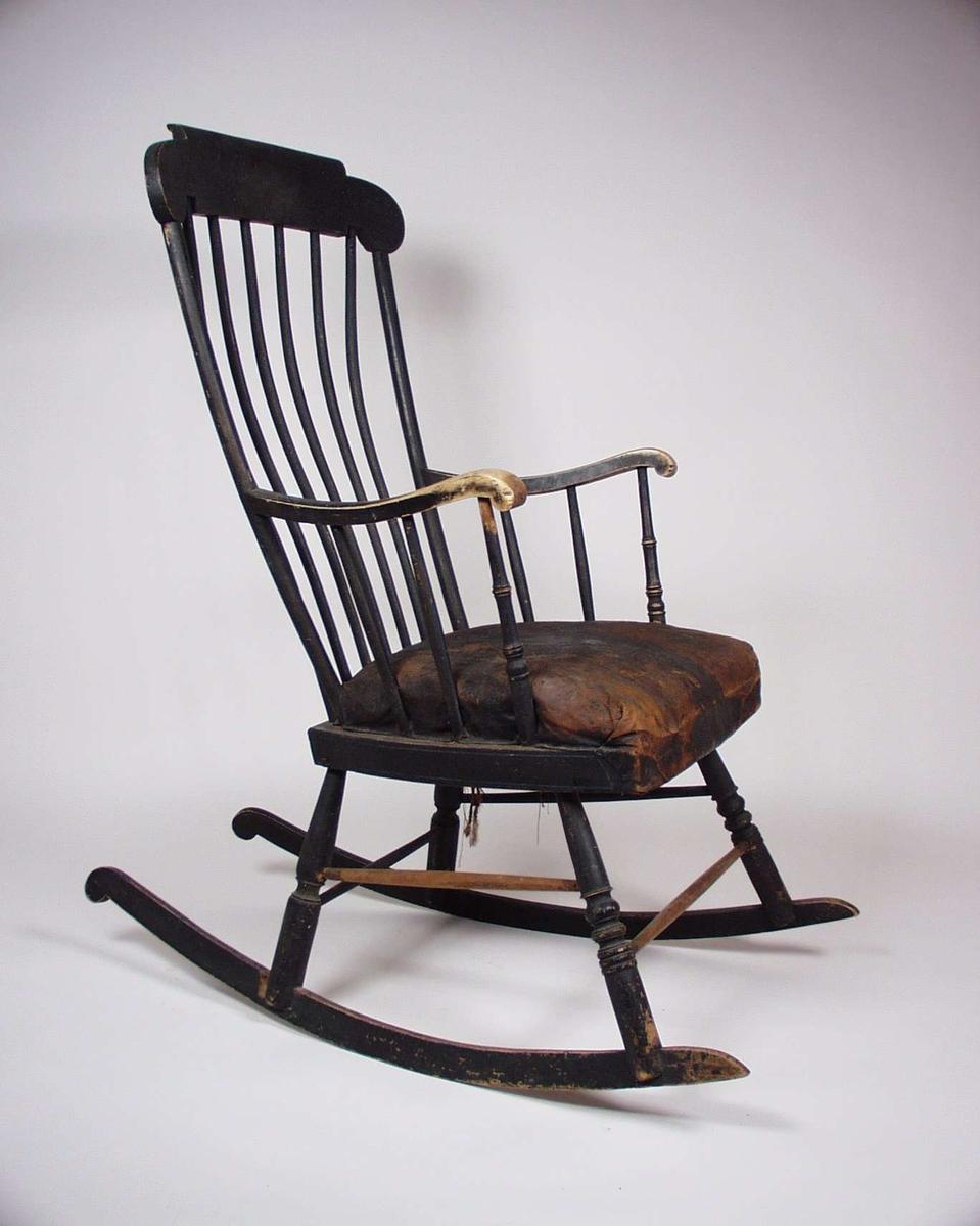 Brunmalt gyngestol i bjørk med stoppet skinnsete og dreide bein. Setet er trolig stoppet og skinntrukket en stund etter at stolen ble laget.
