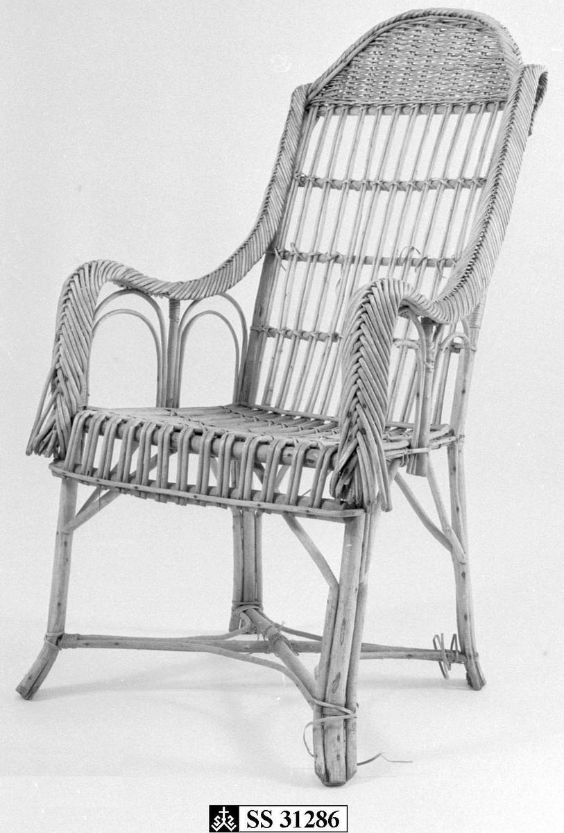 Kurvstol  laget av bjørk og manilla.  Beina har kryssforsterkning. Flettede armlener og dobbelte spiler i sete og rygg.