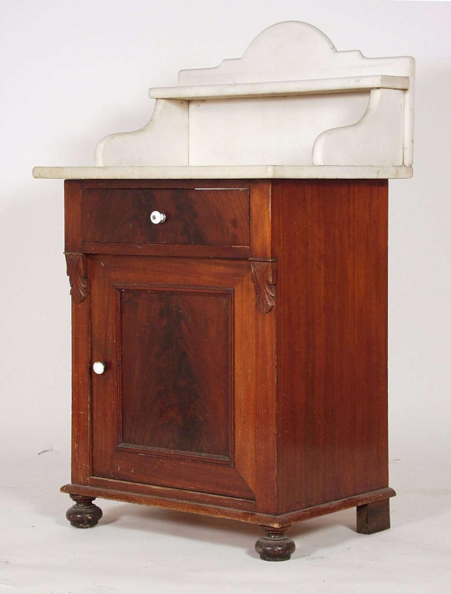 Møbelet er i tre,furu og mahogny-finèr. Toalettskapet er 71,2 cm høyt, med hyllen over måler det 104cm. Hyllen er av marmor. Møbelet har et skap og en skuff, med hylle av kryssfinèr.