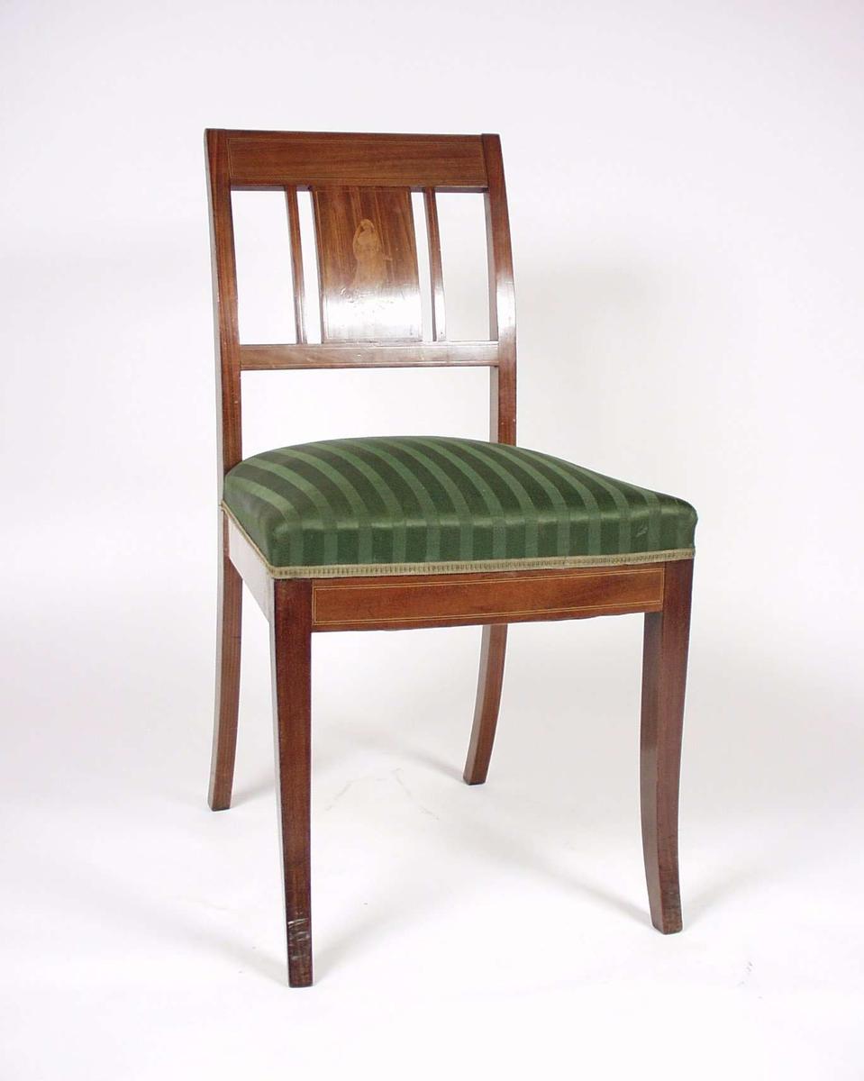 Stolen er av tre med stoppet sete i grønt ulltrekk. Stolen har intarsia i ryggbrett med motiv av gresk dame.