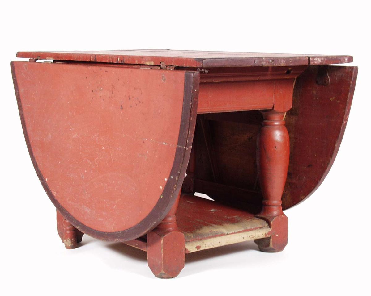 Et klaffebord i furu som er blitt malt rød med smal svart kant på bordplaten. Bordet har fire dreide ben og en underplate som binder klaffebordet sammen. Hver side av bordet er det grinder som holder klaffene oppe.