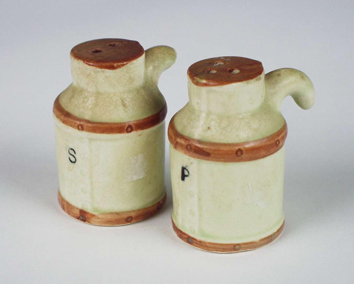 To små beholdere i keramikk. Hull i bunnen med plastlukking. Små ører til håndtak. Den ene er brukket.