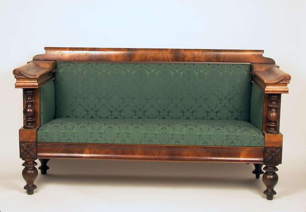 Brunbeiset sofa med stoppet sete, rygg og vanger. Stoffet er grønt. Stilen er en blanding av biedermeier og historisme.