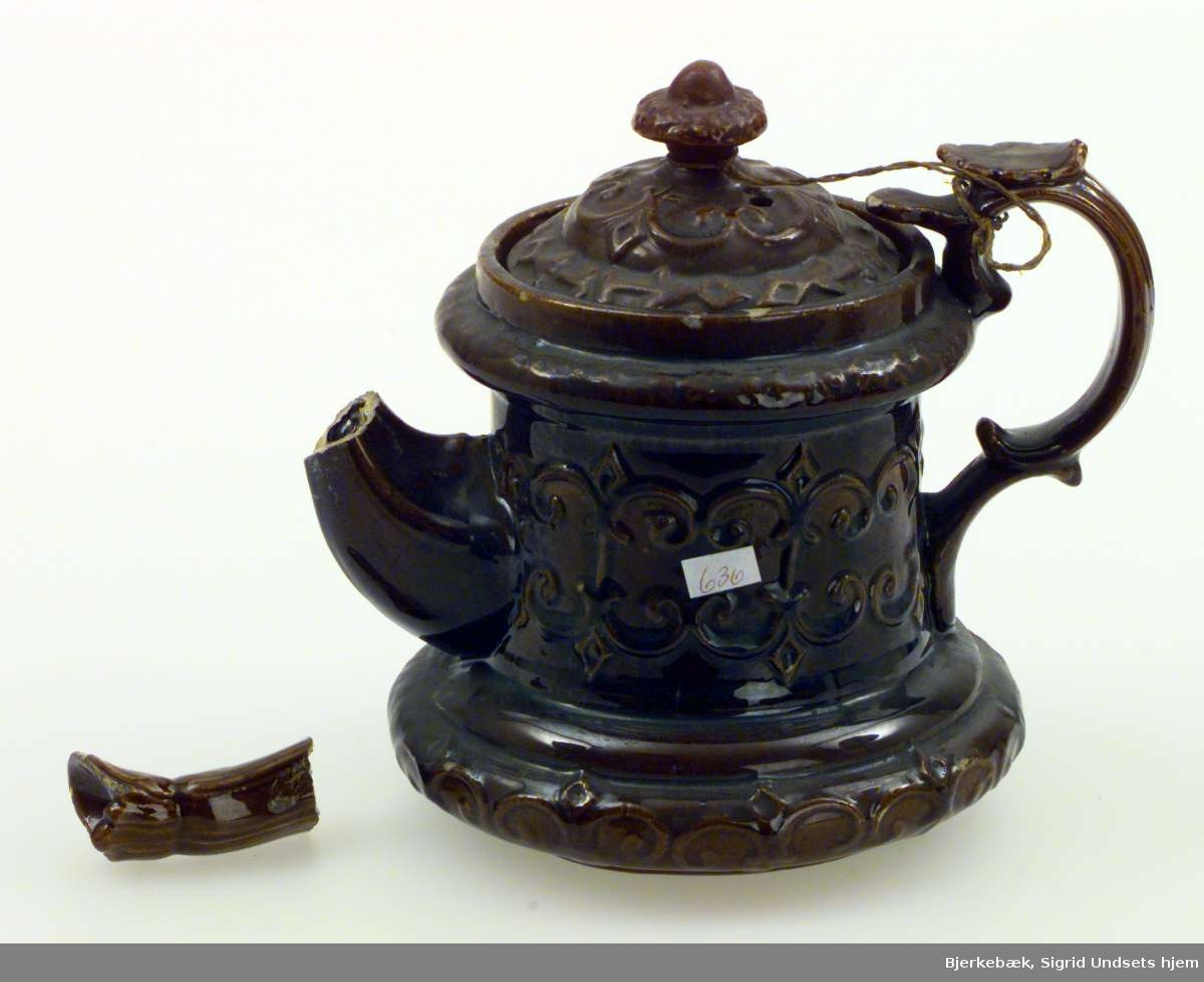 Tekanne i keramikk (steingods) med støpt dekor. Kannen er brun. Lokket er festet til hanken med hyssing. Formen er rund. Kannen er videst i 'foten'.