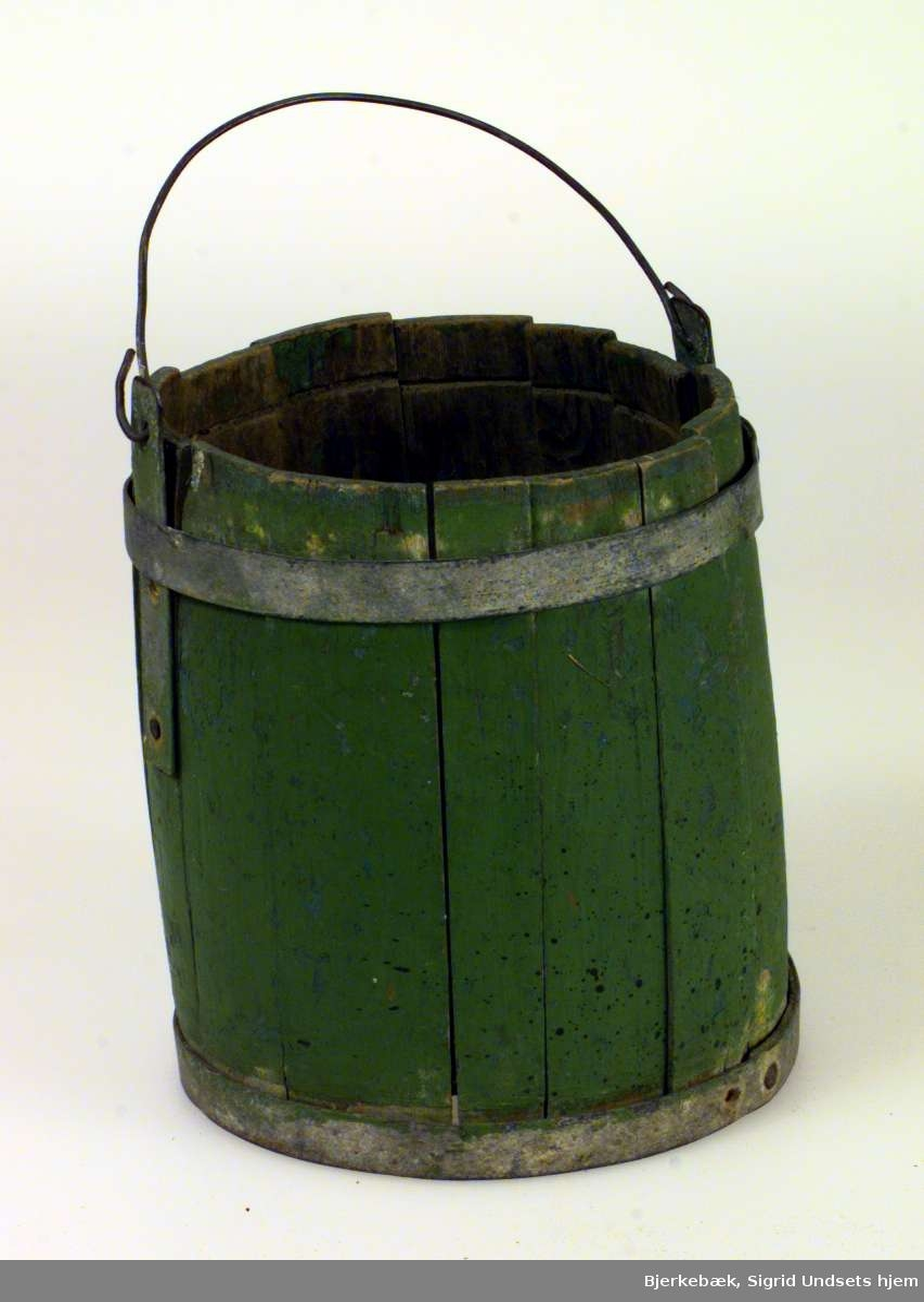 Svakt tønneformet beholder. Den har staver av tre, men gjord og tverrhank av metall. Bøtten er grønnmalt. Den mangler sannsynligvis en innfelt plate i toppen. Bøtten er defekt.