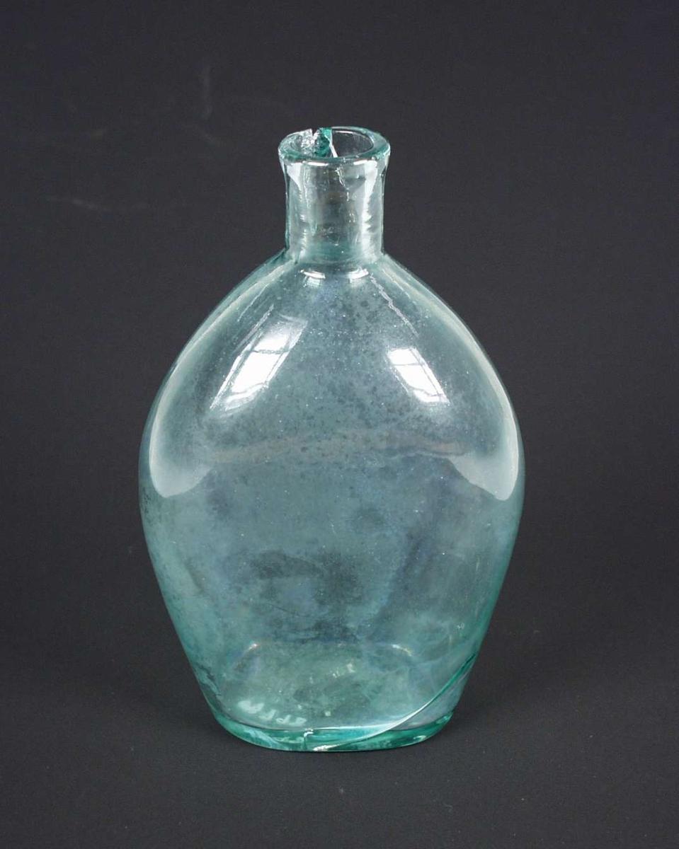 Flasken (jaktflaske?) er av grønt glass. Den er rund og flat. Flasken er defekt.