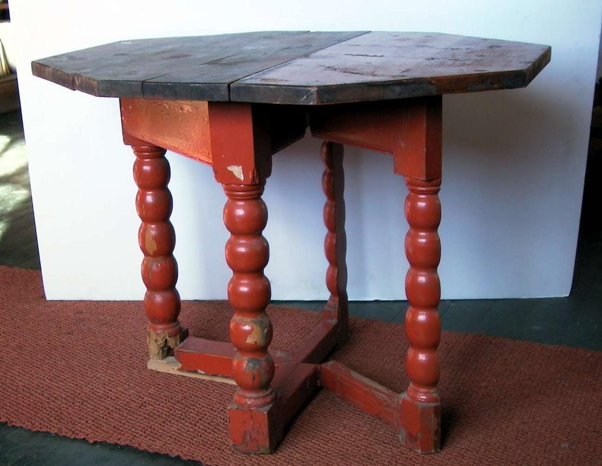 Åttekantet klaffebord med fire ben og benforsterkning. Bordet er rødmalt. Bordplaten er stygg. Treverk er slått av på foten. Malingen er avslitt.