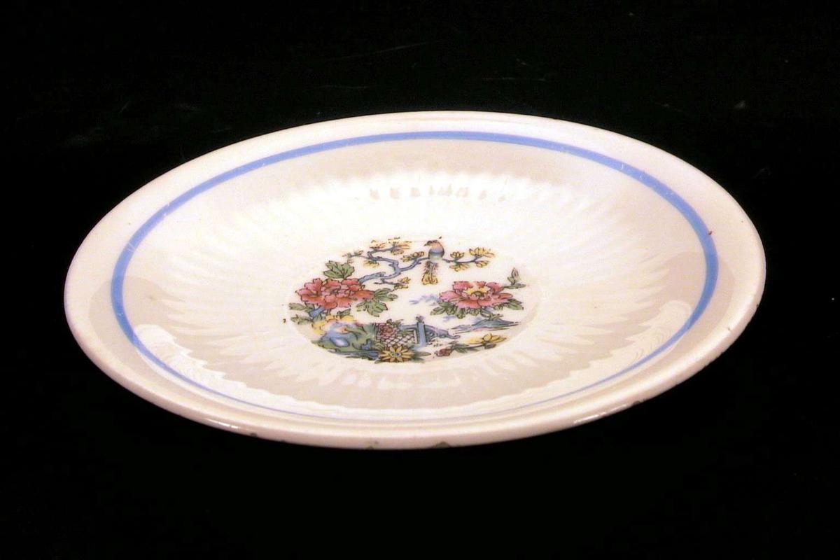 Skål med hvit glasur og østen-inspirert dekor i blått, rødt, gult, grønt.