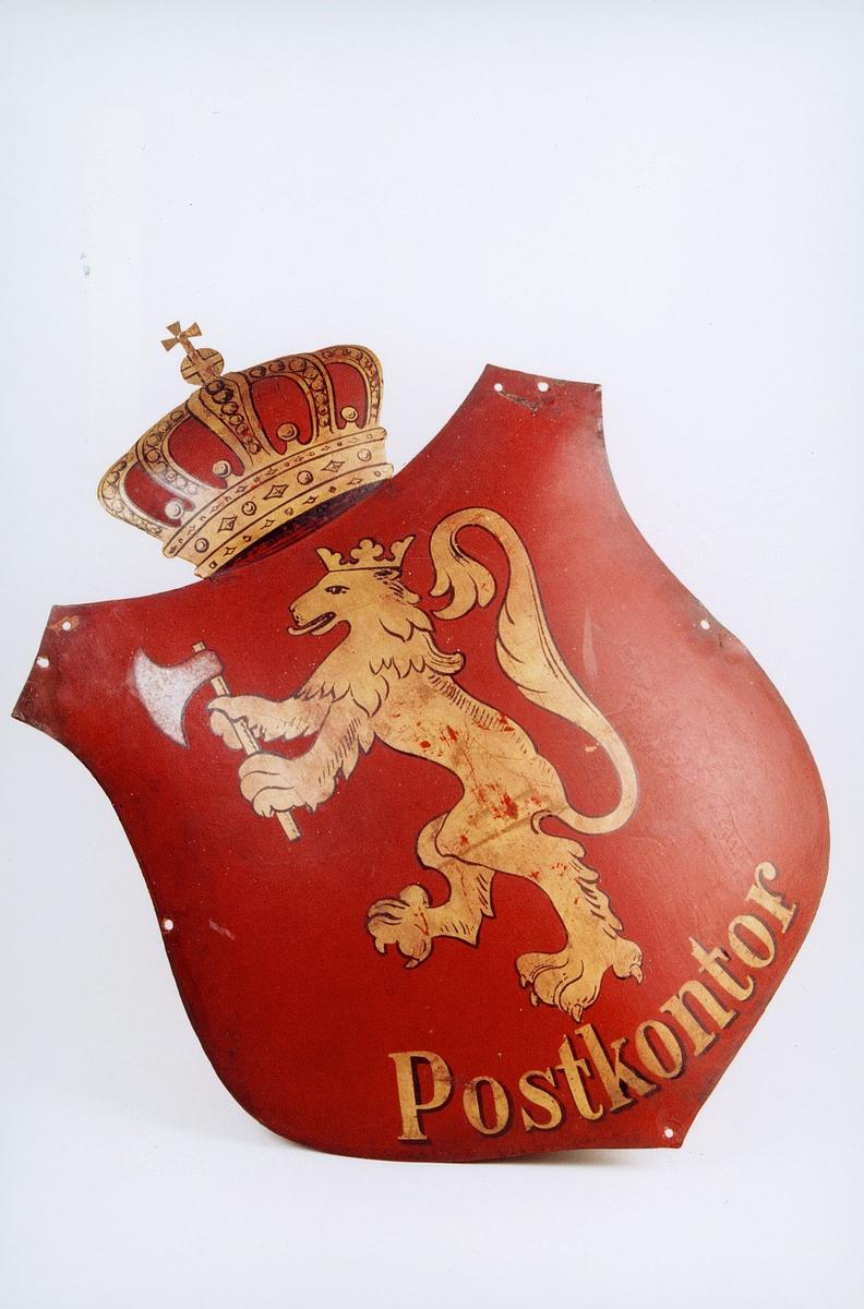Postkontorskilt av blikk, rødmalt med krone, løve og bokstaver i gull.