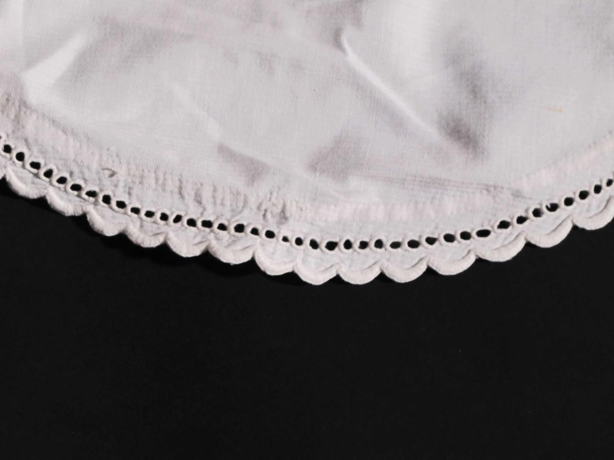 Sirkelformet fasong, forkanten tunget og brodert.  knyttebånd under haken med tungete ender. Bomull, hvit.