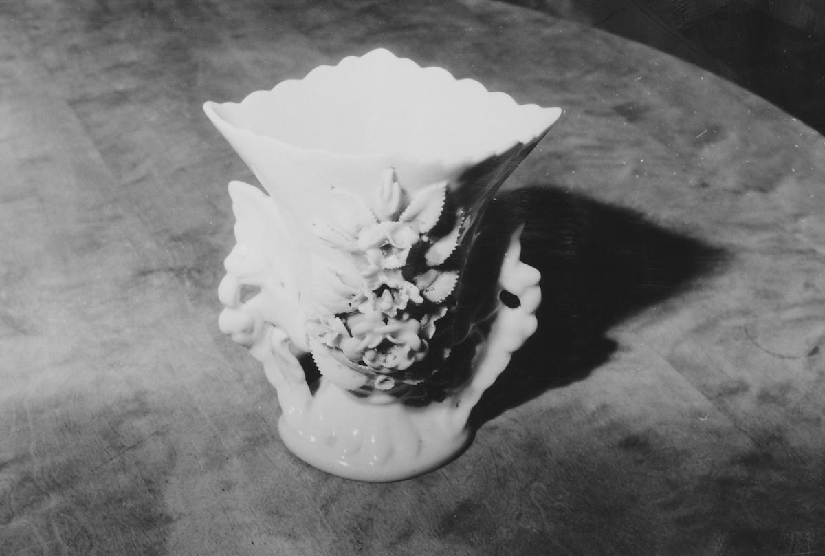Fot; korpus elipseformet tverrsnitt; på sidene ører; bølget munningsrand  m. plast. dekor. På forsiden kraftig plast. blomsterdekor.
