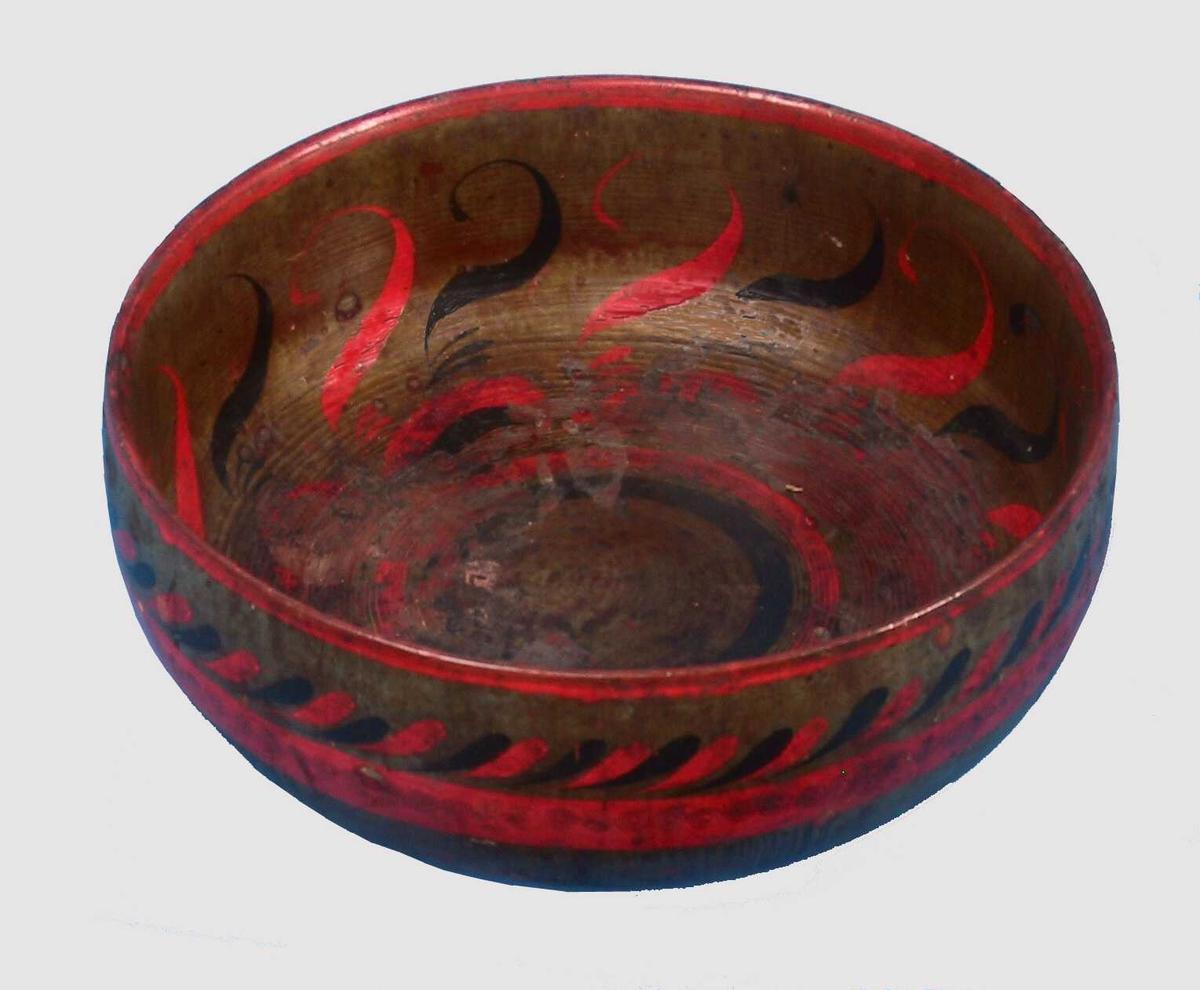 """Russebolle.  Tung,   dreiet  bolle med synlige riller, dekorert i engelsk rødt, sort, gult  på  gulgrønn (""""forgylt"""")  bunn.   Tilstand: innvendig dekor en del avslitt, et par små sprekker  i  stetten."""