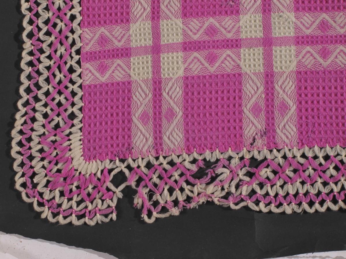 Bordduk,  Bomull  , maskinvevd i vqffelmønster, hvitt og rødlilla.   96 x 91.  Firkantet liten duk i bløtt materiale, som et  skuldersjal med kantbord av åpne ruter, i hvitt  og rødlilla som duken.  Tilstand: god.