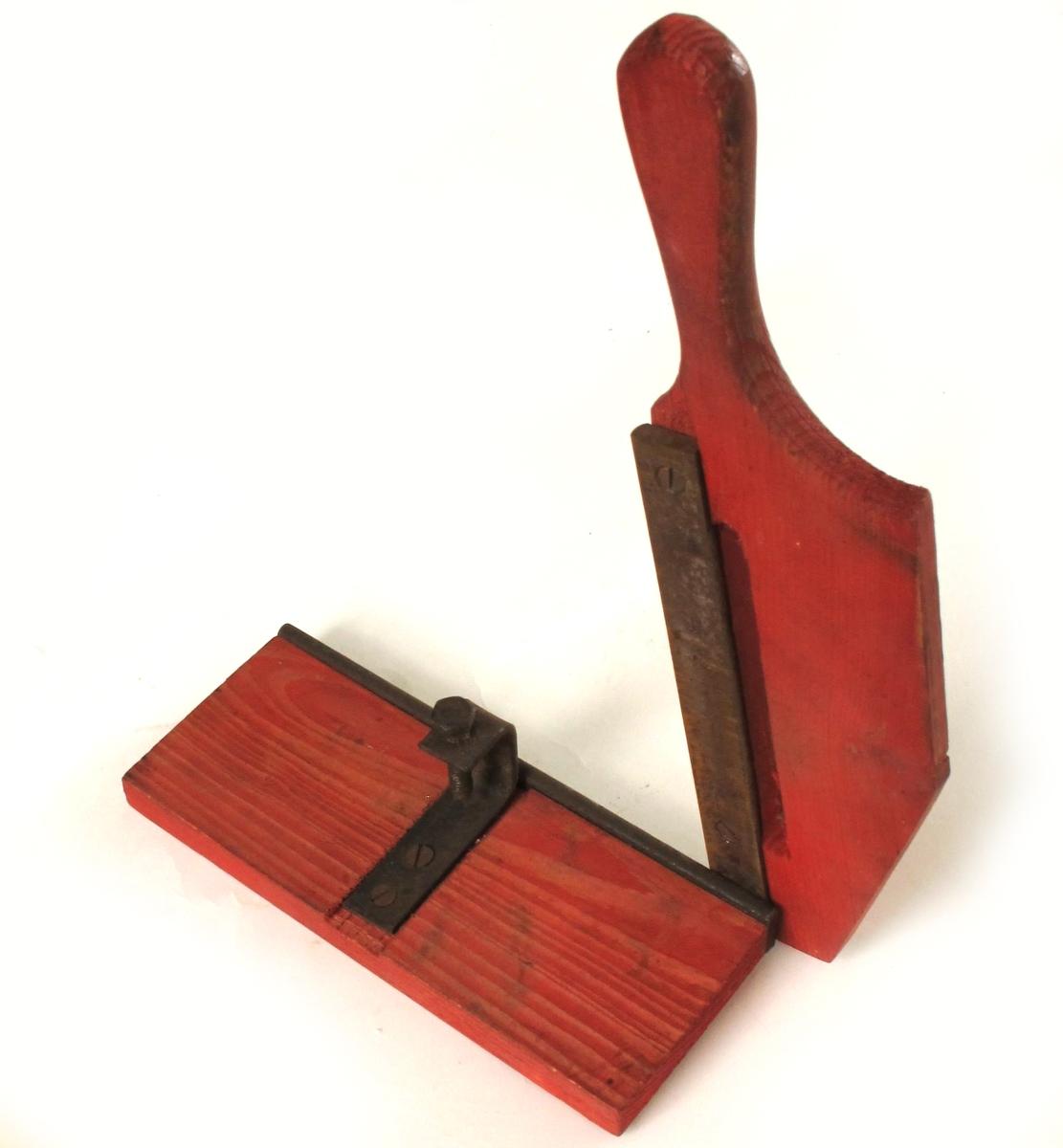 Skjæremaskin for tobakk,  fra krigen 1940-45.    Furu,  rødmalt,   jernkniv.    Kniv uten skarp egg. Form som en papirskjærer,  med håndtak/kniv langs den ene langside. Stilleskrue pm.  Tilstand: jernet rustent. Virker lite brukt.