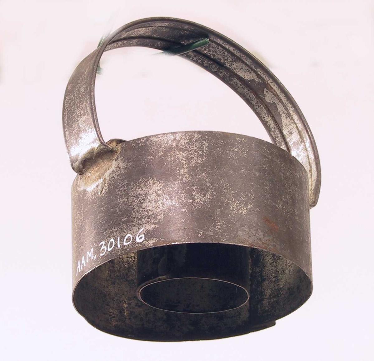 Liten sylinder av tynn jernplate med en større utenfor, festet sammen med et bånd av jern på tvers over begge og et håndtak festet ved hver ende av båndet.
