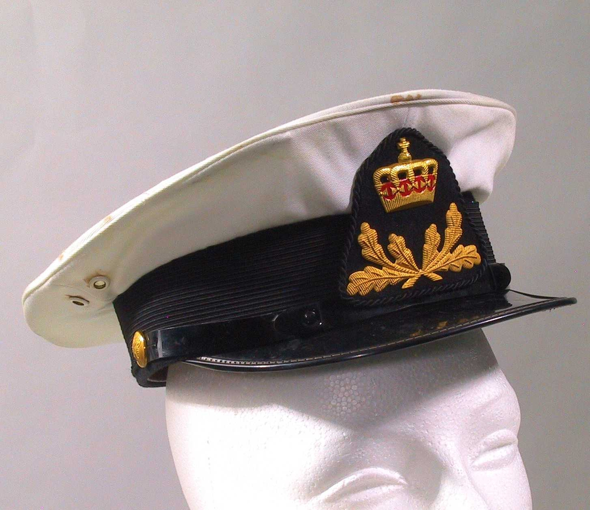 Luemerke i metall formet som en krone, med stiliserte greiner under.