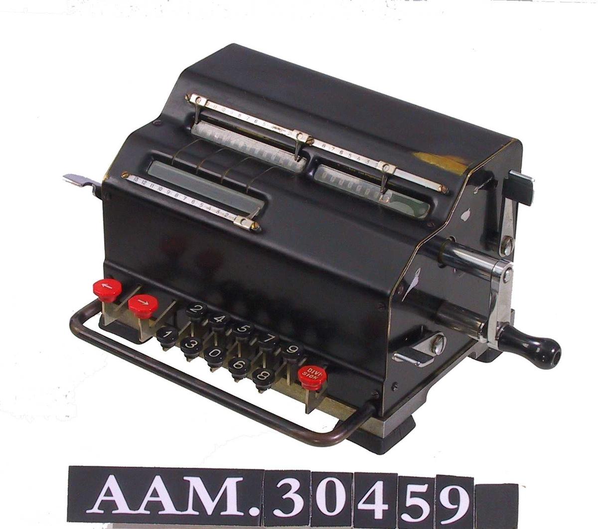 Form: Liten kasse med rektangulær grunnflate, overside med 2 høydenivå, taster stikker ut nederst på fremsiden, bøyle foran disse. Sveiv på høyre side.