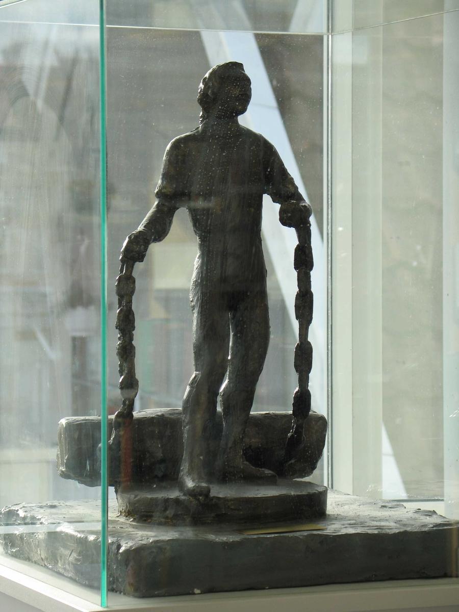 Christian Lofthus som tukthusfange i lenker.  Mannen står med armene halveis ut til sidene, og lenkene han sleper på henger ned.
