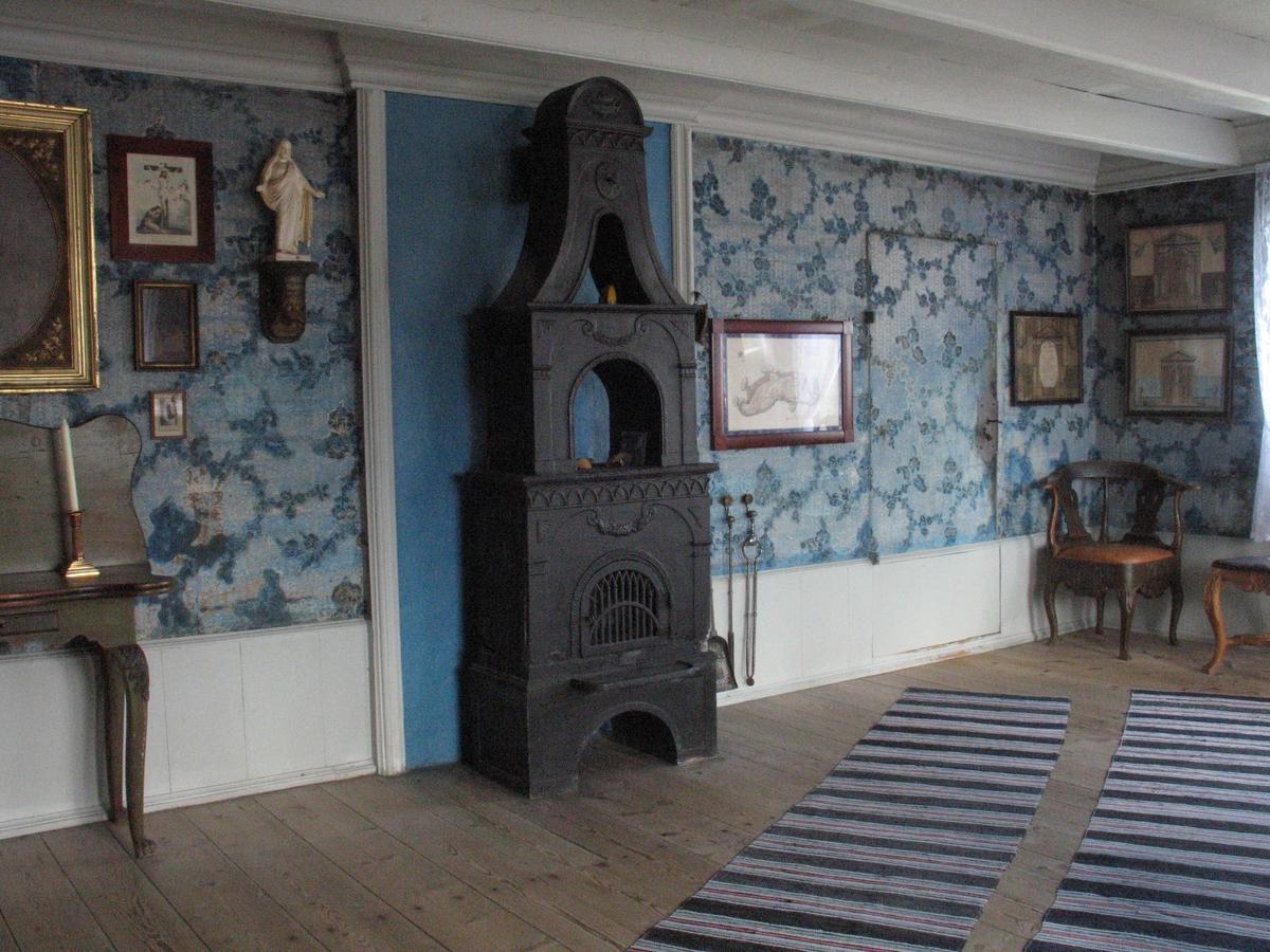 Merdøgaard. Interiør storstua. Bilder på veggen, ovn, velurtapet, brystpanel.