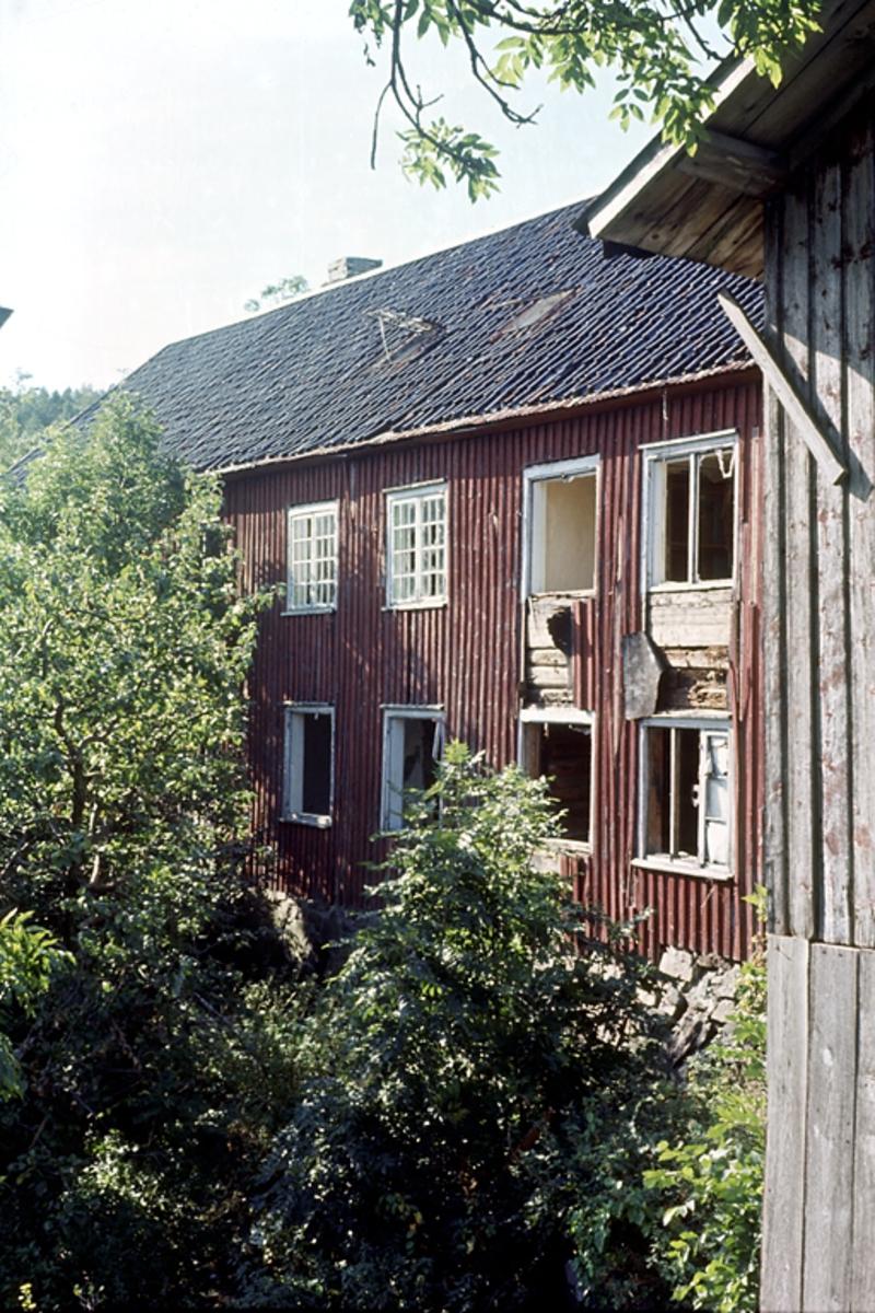 Nedeneshus. Saltrød gård. Rødmalt husvegg, hage og trær. Fotografert før riving.